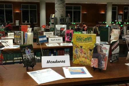 Image of display with a tribute to Honduras, featuring books, factsheets, and miniature flag replica.